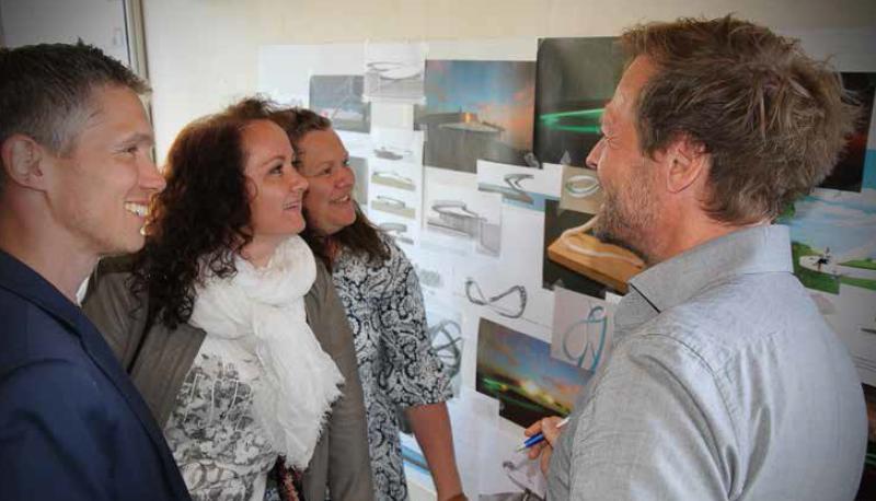 Foto av fastboende og arkitekten foran illustrasjoner av energiinstallasjonen.