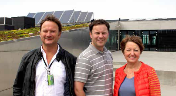 Foto av avdelingsleder Vidar Dramstad, seniorrådgiver Anders Fugleneb og direktør Toril Mølmen fra Innovasjon Norge foran solfangerne på Inspiria